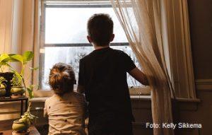 Ninos en casa mirando por una ventana